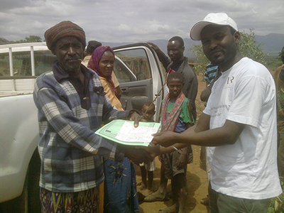 pastoralist receiving insurance policy doc