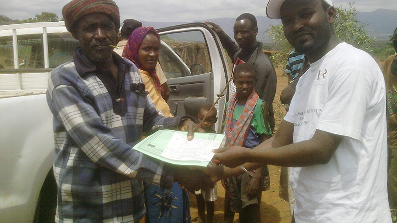 pastoralist receiving insurance policy